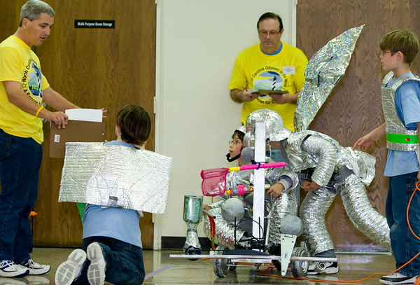 Officials Drew Dangelo, left, and Larry Lautzenheiser go over the cart built by St. Mark Catholic School's 5th grade team from Wilmington, left to right, Devon Amos, Joseph Keller, Henry Kunz, Andrew Sawyer and, not pictured, Tyler Smith and Daniel Antonelli.  Saturday at the Odyssey of the Mind competition on ECU's campus.  (Jenni Farrow)