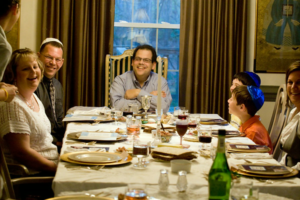 Bryan Weil, center, leads the group gathered for the Seder, the Jewish feast celebrating the passover, Wednesday evening at his parent's home in Greenville.