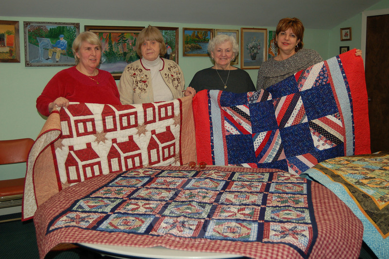 From left is Ida Reiske, Sylvia Krug, Terry Curry, and Senior Center Director Marilyn Place, who are all members of the Newtown Senior Center Quilters. They are displaying the quilts they have worked on since last January for the Quilts of Valor project. The quilts will be sent to Washington state to comfort injured soldiers at a VA hospital there.  (Crevier photo)