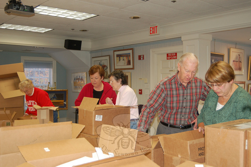 From left, Barbara Gorham, Marg Studley, Marj Aitchison, Alex Aitchison, and Colleen Honan, members of the Christmas Lighting luminaria committee, pack up the new, safer burning votive candles and luminaria boxes for distribution to Main Street and Glover Avenue residents, to be lit the evening of December 4. Committee chairperson Diana Johnson said residents on those streets should all have received the boxes by November 25. Call Ms John-son at 203-426-5418, Janet Woycik at 203-426-1561, or Amy Mangold at 203-426-4340 with questions.  (Crevier photo)