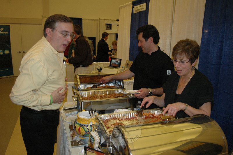 Numerous restaurants and food vendors kept the crowd at Destination Newtown well fueled with samples and specialties. Here, John Tambascio and his mother, Louise Tabascio, representing Tambascio's Italian Grill, dish it out for Gus Thanasoulis, co-owner of Newtown's Senior Helpers.  (Voket photo)