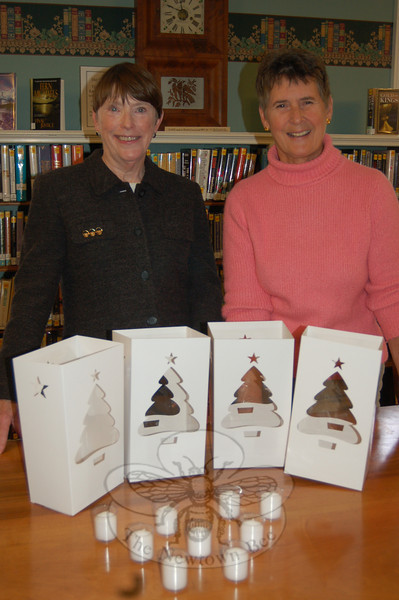 Ram Pasture Tree Lighting committee members Janet Woycik, left, and Diana Johnson, display the new votive candles that will be used this year in luminaria placed along Main Street, Elm Drive, and Ram Pasture for the December 4 tree lighting ceremony.  (Crevier photo)