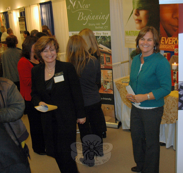 Carol St. Amand-Romer, left, owner of A New Beginning in Bethel, chats with marketing specialist and Newtown resident Helen Brickfield as both staff the day spa's booth at Destination Newtown on November 10.  (Voket photo)