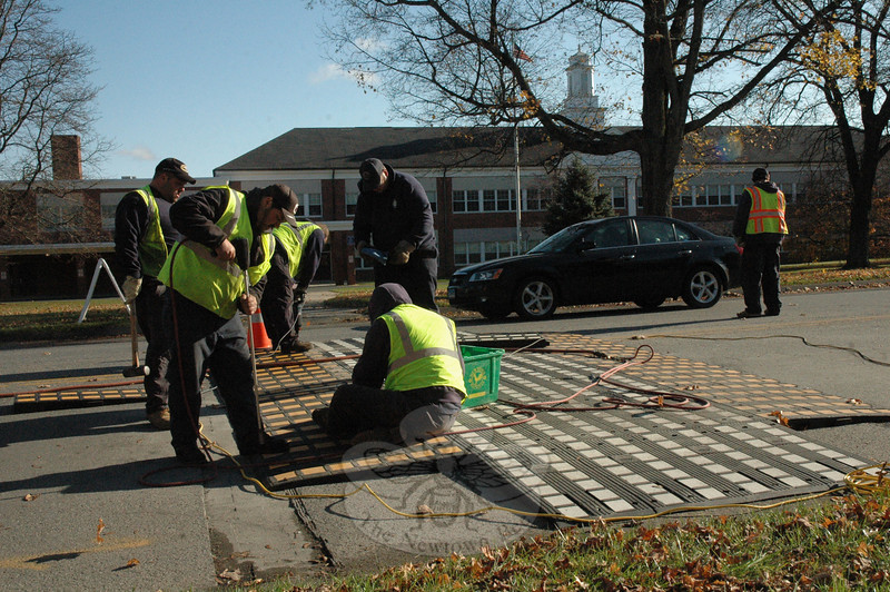 """Town road crew members installed a """"raised crosswalk"""" on Friday, November 6, on Queen Street in front of Newtown Middle School. The previous day the crew had installed a similar device on Glover Avenue. Raised crosswalks are intended to give pedestrians a safe place to cross the street and also serve as broad speed bumps which generally slow traffic. State law requires motorists to yield to pedestrians who are standing in crosswalks. Areas near raised crosswalks are posted with signs and markings alerting motorists of their presence. The raised crosswalks are being tested for their practicality.  (Gorosko photo)"""