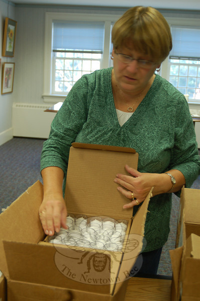 Colleen Honan counts candles being packed into a box to be distributed to residents surrounding Ram Pasture in time for the town's tree lighting on December 4.  (Hicks photo)