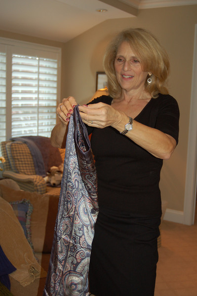 A square scarf folded neatly lengthwise, then wrapped twice about the neck and tied to the side adds a polished look to a business outfit. Positive Reflections wardrobe coach Pam Friedlander cautions that the printed side of the scarf must be kept facing out.  (Crevier photo)