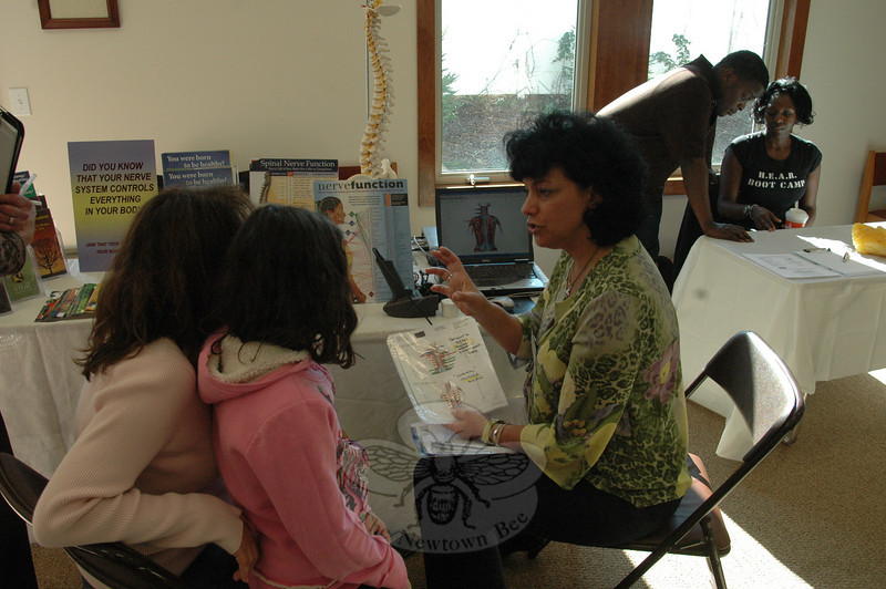 Dr Sharon Weicman of Main Street Chiropractic discussed diagnostic nerve scanning with Newtown resident Debra Nahmias and her daughter Meghan during the recent health fair at Congregation Adath Israel.  (Voket photo)