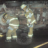 Two Dodgingtown firefighters inspect the wreckage at a rollover accident that occurred about 6:22 pm November 19, on a wet Boggs Hill Road, just south of its intersection with Wil-low Brook Lane. Police said motorist Gabrielle DiTullio, 18, of Redding was driving a 1997 Chevrolet Tahoe SUV on Boggs Hill Road, and while negotiating a curve in the road, she lost control of the vehicle. (Gorosko photo)