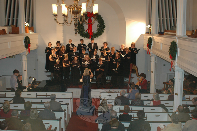 Mary Andreotta directs the Newtown Choral Society in this 2006 photo. Ms Andreotta has returned after a one-year sabbatical for her tenth season directing the local singing group. Newtown Choral Society will present its annual winter concert on Sunday, December 6, at 4 pm, at Newtown Meeting House.  (Bee file photo)