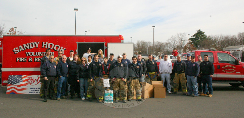 For the ninth time, volunteers from all five of Newtown's volunteer fire departments collaborated on a pre-Thanksgiving food drive last weekend. Karin Halstead, EMS Captain for Sandy Hook Volunteer Fire & Rescue, arranged to have members of Hook & Ladder, Sandy Hook, and Hawleyville departments — some of whom are seen here — stood by at The Big Y on Queen Street on Saturday, November 21, where they received donations from shoppers for five hours. Meanwhile, Ms Halstead also arranged for members of Botsford and Dodgingtown to receive similar donations at Stop & Shop.  (Hicks photo)