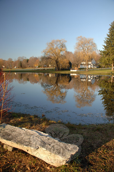 A stone bench overlooks reflections held on Hawley Pond's still surface. Although a stream of traffic along Route 25 rippled through the background and breeze jostled dry leaves, the reverse image on the pond remained unchanged.  (Bobowick photo)