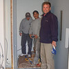 John Madzula II of JSM Associates designers and builders in Newtown stands by as ThyssenKrupp Access contractors Ben Hall, left, and Thanh Nguyen demonstrate the new accessibility lift being installed in Newtown Meeting House. Following a month of preparation by JSM, installation of the elevator began Wednesday afternoon, November 18. Workers expected the lift to be fully operational by the weekend.  (Crevier photo)