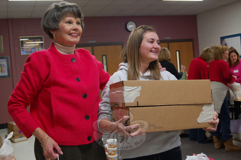"Newtown Middle School Principal Diane Sherlock, left, and eighth grade student Emily DeGirolamo sought a helper to help carry Emily's ""too many to count"" tubs of cookie dough on Wednesday, December 2.  (Hallabeck photo)"