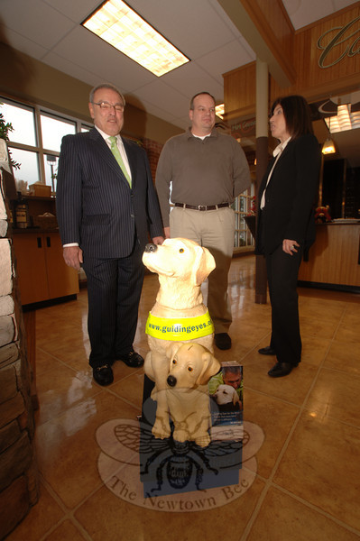 Resident Howard Lasher, left, a Guiding Eyes for the Blind volunteer and supporter, met with the organization's Vice President Lisa Deutsch on Friday, December 4. Between them is Caraluzzi's store manager Greg Johnston. The group stands beside a donation dog that sits in the store's lobby where Ms Deutsch hopes to raise funds to maintain the guiding eyes programming.  (Bobowick photo)