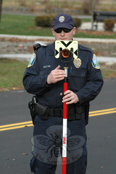 Police Officer Jeff Silver holds a target that police use with laser-based measuring devices to record data at the scene of serious motor vehicle accidents.  (Gorosko photo)