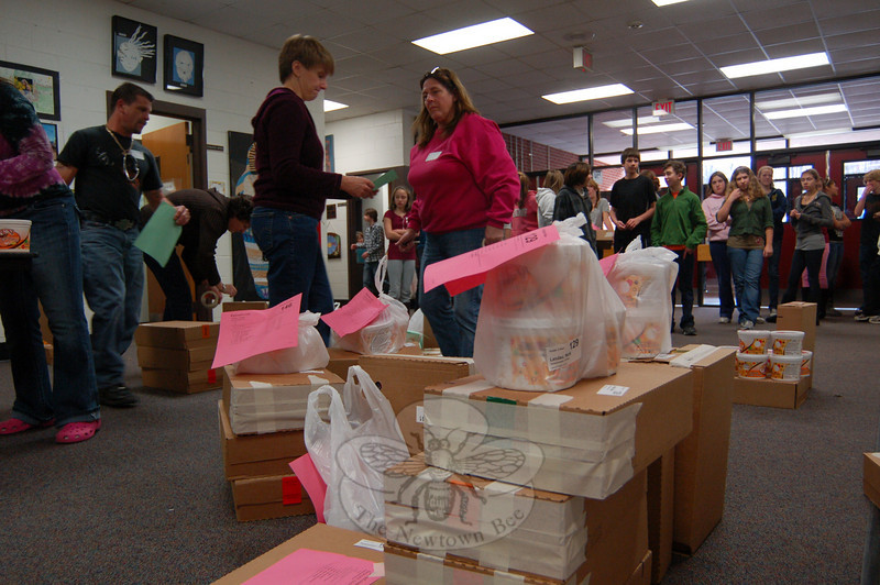 Parent volunteers worked on Wednesday, December 2, to organize and distribute tubs of cookie dough at Newtown Middle School from this year's Cookie Dough Sale.   (Hallabeck)