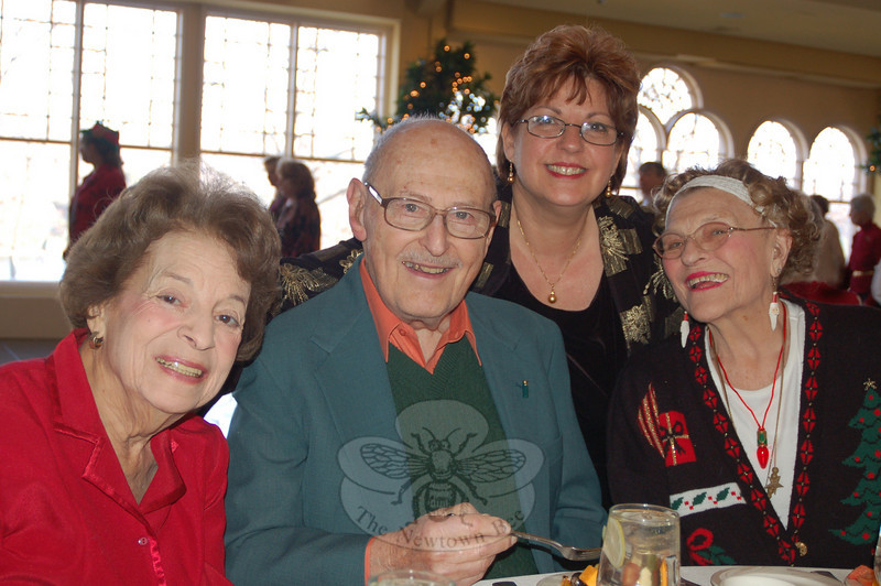 From left, Edna and Dr Gene Marks, Senior Center Director Marilyn Place, and Glenna Rees share a moment together at the Senior Center holiday party on Tuesday, December 8.  (Crevier photo)