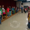 "The entire student body assembled in the cafetorium of Head O' Meadow School on Friday, December 4, to learn news from around the school. Members of Rosemarie Costello's fourth grade class took turns sharing school news. Head O' Meadow Principal William Bircher (center) led the students and staff in singing ""My Country, 'Tis of Thee.""  (Hallabeck photo)"