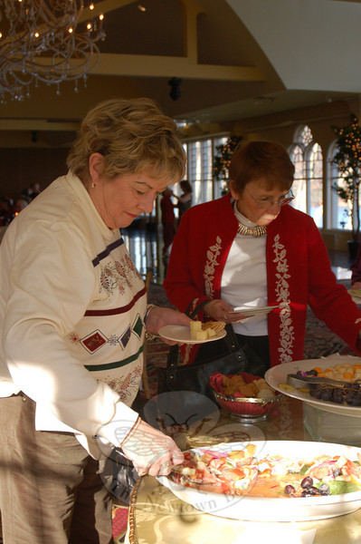 Bernadette Schiavone, left, and Nancy Schoch enjoyed the selection of salads and cheeses at the appetizer buffet during Newtown Senior Center's recent holiday party.  (Crevier photo)