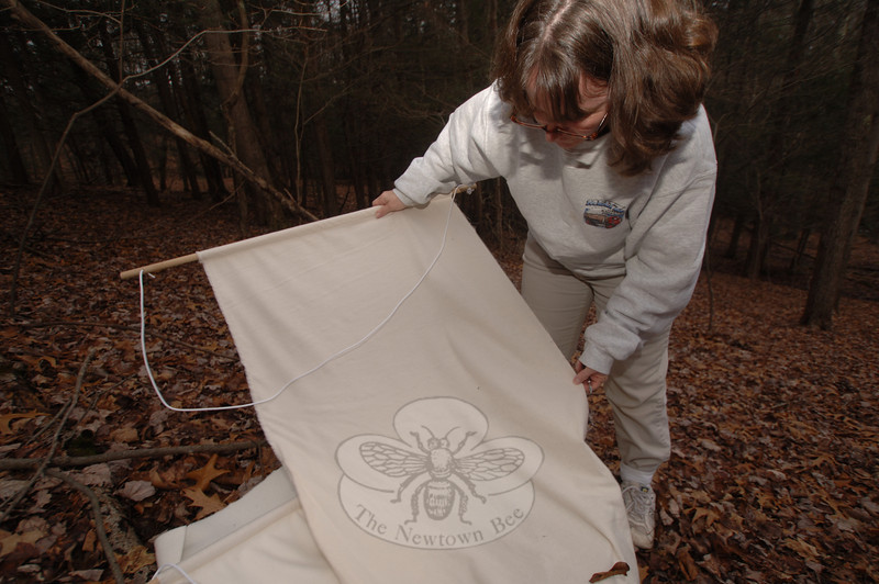 Leaning close to look for ticks that had caught in a felt sheet she dragged through the un-derstory at Orchard Hill Nature Center on Thursday, December 3, Health District Director Donna Culbert was surprised to find nothing more than leaves and forest debris after her first few attempts.  (Bobowick photo)