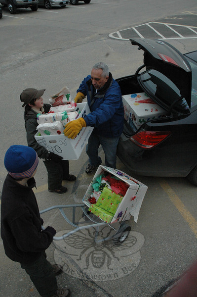Two boy scouts and an adult loaded the spacious truck of a large sedan with gifts bound for a local needy family on December 17 during The Newtown Fund's annual Depot Day.  (Gorosko photo)
