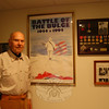 Dr Irving Freedman stands by a 50th anniversary poster from 1994 honoring the Battle of the Bulge. Dr Freedman spent the 1944 holiday season isolated in a Belgium farmhouse with five other members of his bomb squad, as the final German offensive raged through the area.  (Crevier photo)