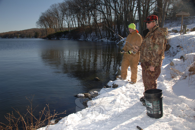 With buckets and nets at their feet where they had worn a patch of trampled snow along the water's edge, T.J. Stuart and Dan Butler reeled in their lures for one cast after another while they fished the frigid Taunton Pond on December 21.  (Bobowick photo)