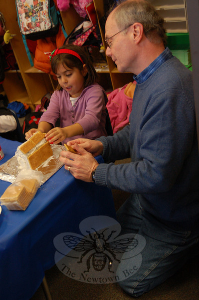Ken Walters, right, helped Sandy Hook School student Chris Berke make her gingerbread house on Friday, December 18.  (Hallabeck photo)