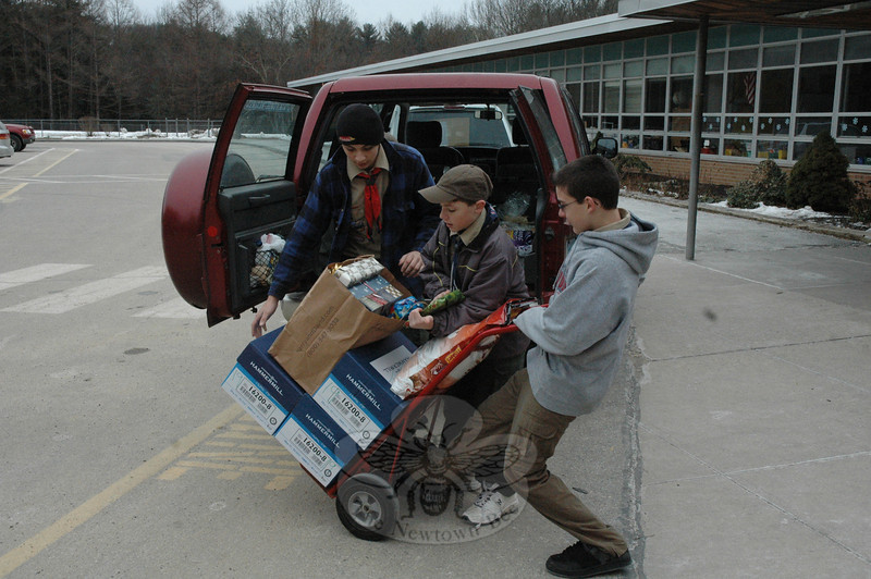 Boy Scouts hefted numerous brightly wrapped gifts into waiting vehicles for delivery to needy families across town during The Newtown Fund's Depot Day.  (Gorosko photo)