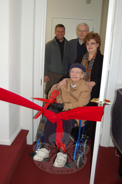 Mary Mitchell prepares to cut the ribbon Monday, January 4, at the soft opening ceremony for the handicapped entry elevator recently installed at the Newtown Meeting House. Looking on with her, from left, are John Madzula of JMS Construction, Heritage Preservation Trust, Inc President Don Studley, and Brookfield voice teacher Pamela Hoffman. Ms Mitchell recognized the need for the lift and two years ago donated seed money to fund the installation of the elevator. Ms Hoffman organized several musical fundraisers at the Meeting house, which she uses for her students' vocal presentations.  (Crevier photo)