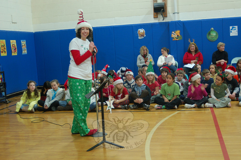 Middle Gate Elementary School Music teacher Gate Elementary School teacher Tina Jones led students in singing, playing music and sharing holiday riddles during the school's annual schoolwide holiday sing-along.  (Hallabeck photo)