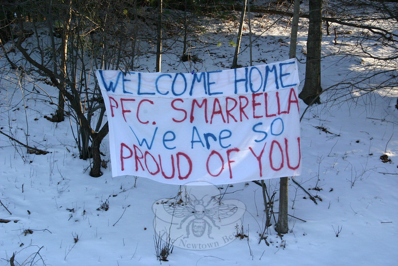 """James and Cathy Smarrella put this banner out at the end of their driveway on Philo Curtis Road to welcome their son, US Marine Corps PFC Matthew Smarrella, home recently. PFS Smarrella left Iraq on December 10, and his father picked him up in Fredericksburg, Va., on December 22, just in time for Christmas and New Year's. PFC Smarrella spent about two weeks at home, his father told The Bee this week, and left on Monday morning, January 4, to report back for duty. """"We saw a lot of people slowing down to read the banner, and people would honk their horn if they saw us outside,"""" James said this week. """"Someone even tied a balloon that says 'Thanks' to the banner. We don't know who did it, but that was nice to see.""""  (Hicks photo)"""