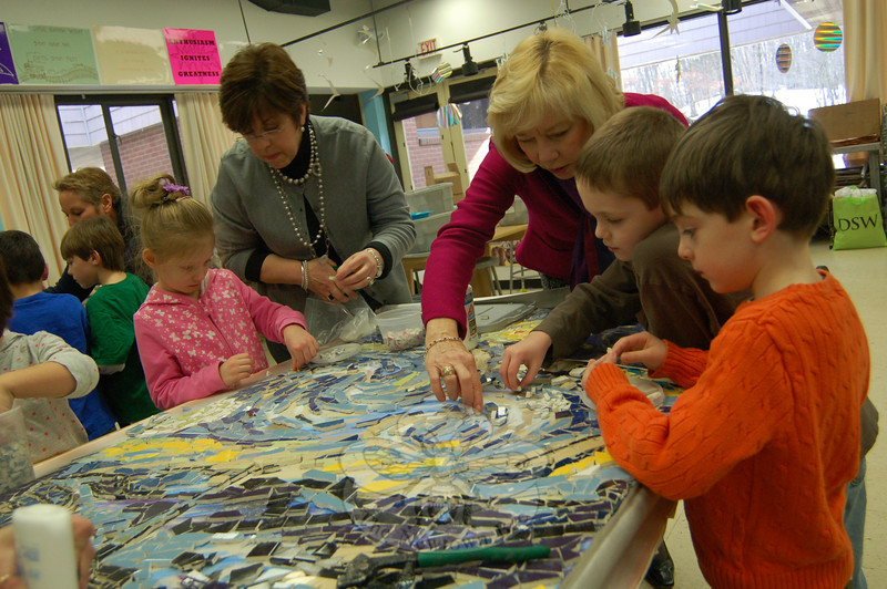 """Superintendent of Schools Janet Robinson, middle right, helped Head O' Meadow first grade students place ceramic tile pieces on what will be an art installation at Head O' Meadow. The finished project will be a four panel re-creation of Van Gogh's """"Starry Night."""" (Hallabeck photo)"""