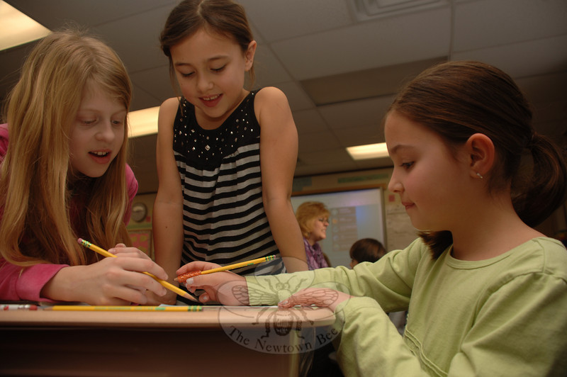 Second grader Grace Bianco worked with fourth graders Paige Galanis, left, and Ashlyn DeLoughy as they completed Valentine's Day cards for troops overseas.  (Bobowick photo)