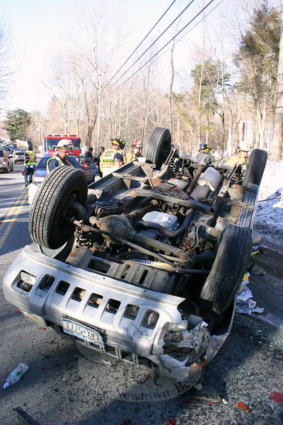 This SUV came to rest upside down on Berkshire Road (Route 34), near Sherman Street, following a two-vehicle collision about 1:04 pm January 9. Police report that motorist Victoria Miller, 24, of Brookfield, who was driving a 2007 Subaru sedan westward on Berkshire Road, stopped for a vehicle in front of her, which was making a left turn onto Sherman Street. Southbound motorist Matthew Buffone, 37, of Tonawanda, N.Y., who was driving a 1998 Jeep Grand Cherokee SUV behind the Subaru, then swerved to the right to avoid hitting the Subaru, but the Jeep drove up an embankment and struck a utility pole, causing the Jeep to roll over, land on its roof, and collide with the Subaru, police said. Both motorists were wearing seatbelts and were not injured, police said. Sandy Hook firefighters and Newtown Volunteer Ambulance Corps members responded to the accident scene. After investigating, police arrested Buffone on charges of driving under the influence and making a restricted turn. Buffone was released on $100 bail for a January 22 court arraignment.  (Hicks photo)