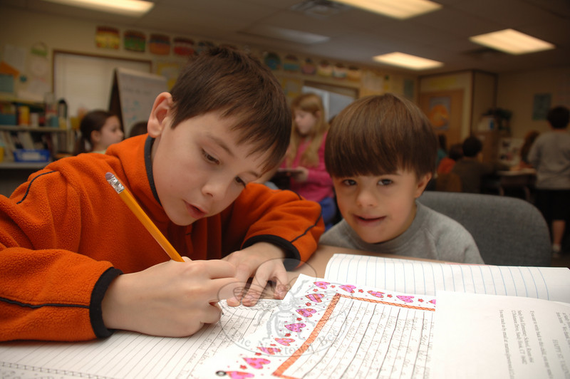 Harry Eppers, grade four, carefully wrote out his words of thanks and appreciation to one of many servicemen and women who will receive a Valentine's Day message from Newtown students this year. Working with him was second grader Matthew Vigneau.  (Bobowick photo)