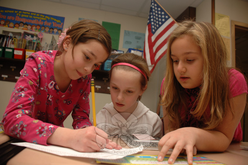 Fourth graders Tara Franklin, left, and Haley Streck, right, worked with second grader Colleen Phaneuf as they created letters for the troops as Valentine's Day approaches.  (Bobowick photo)