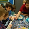 Nicole Snow of The Art Spot worked with Head O' Meadow School first grade students on one of the panels of an art installation that will be hung in the school's front foyer.  (Hallabeck photo)