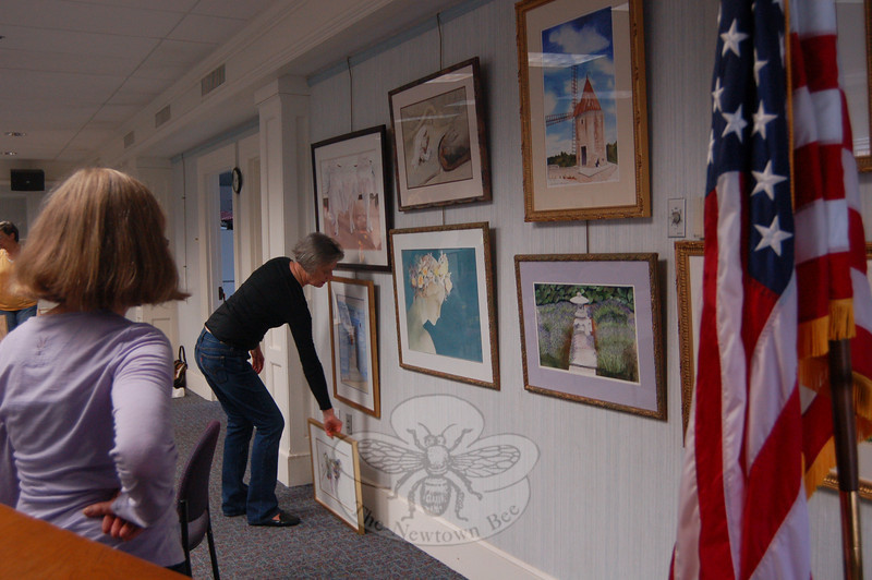"Robyn Dohrenwend, right, hangs a painting for the ""Here's to Painting"" exhibit now on view in the meeting room of the C.H. Booth Library while fellow exhibiting artist Maureen Rohmer, left, looks on.  (Hallabeck photo)"