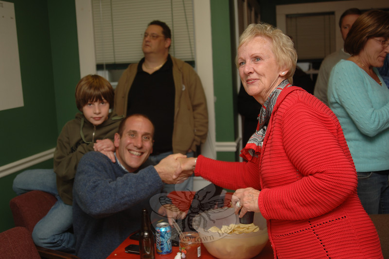 Newtown's new Republican First Selectman Patricia Llodra shares a celebratory handshake with Jeff Capeci, who won a seat on the town's Legislative Council, Tuesday night as she reads the numbers leaning heavily in her favor as party chairman Bill Brimmer pencils them in.  (Bobowick photo)