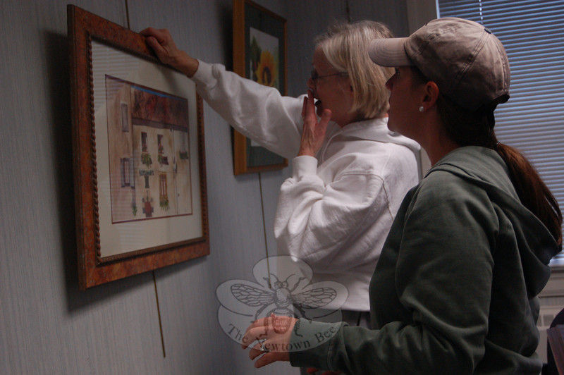 """Martha Glynn, left, hangs a painting with help from Meg Gioffe on Saturday, October 31, for the """"Here's to Painting"""" exhibit now on view in the meeting room of C.H. Booth Library. The public is invited to the exhibition's opening reception on November 8.  (Hallabeck photo)"""