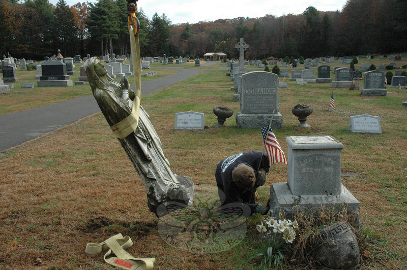 Staff from Brown's Monument Works were at St Rose Cemetery on Monday, repairing stones and other items that had been damaged during a weekend vandalism spree that occurred in the Sandy Hook burial ground.  (Gorosko photo)