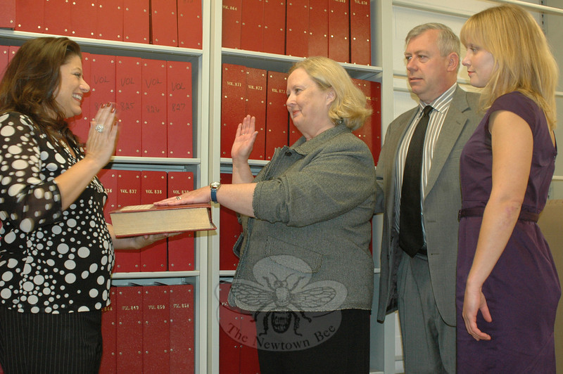 Town Clerk Debbie Aurelia, left, swore in newly elected Judge of Probate Moira Rodgers at 9:30 am, Wednesday, November 4, at Newtown Municipal Center. Ms Rodgers, who won a special election to fill the position vacated when Judge Margot Hall retired, was joined by husband Will, who won a selectman's seat the night before, and daughter Amelia.  (Voket photo)