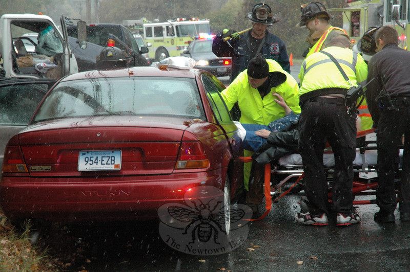 Three vehicles were involved in an accident during snowy conditions about 2:40 pm October 15, at the intersection of South Main Street and Ethan Allen Road. Ryan Zitnay, 17, of 58 Parmalee Hill Road was driv-ing a 1999 Ford Ranger pickup truck southward on South Main Street, as motorist Amalia Caggiano, 87, of Nunnawauk Road, was driving a 1999 Saturn sedan northward on South Main Street. At that time, trucker Nicholas Caruso, 24, of 27 Bennetts Bridge Road, who was driving a 2006 GMC garbage truck, was stopped at a stop sign on westbound Ethan Allen Road at its intersection with South Main Street, police said. The Ford then attempted to make a left turn onto Ethan Allen Road, but it was struck by the ap-proaching Saturn. That impact caused the Ford's rear bumper to be pushed into the windshield of the garbage truck. Newtown Volunteer Ambulance Corps staffers transported Caggiano to Danbury Hospital to be treated for injuries. Zitnay and Caruso received medical treatment at the scene. Zitnay received an infraction for making a restricted turn. Botsford and Hook & Ladder firefighters responded to the accident.  (Gorosko photo)