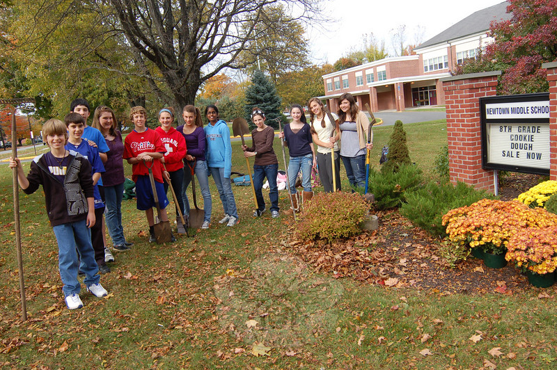 """Members of Newtown Middle School Student Council stayed after school on Tuesday, October 20, to help in the yearly """"Fall Beautification"""" effort. Student Council advisors Linda Dale Mulholland, Nadia Papalia and Rose Ann Beck oversaw the effort, which planted mums near the sign now reminding students and residents that the Cookie Dough Sale is still underway until October 30.  (Hallabeck photo)"""