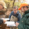"Heads bent together, Bill Bennett, left, and George Hansen, both of Trout Unlimited, helped test for macroinvertibrates in Newtown's streams on October 17. Also standing on the banks of the Pootatuck River, one of several testing spots on Saturday, was Harrison Pease, also with Trout Unlimited. While they collected samples indicating a good stream life, ""There is always room to improve,"" said Mr Bennett. Such water-dwelling insects help testers determine water quality. The town's Conservation Commission organized the morning's sam-pling.  (Bobowick photo)"