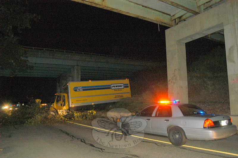 A large box truck landed on Hanover Road about 3:50 am Saturday, Oc-tober 17, after its driver, Todor Mijailovic, 22, of Chicago, switched travel lanes and then lost control of the truck while driving it east-bound on I-84. The truck went off the highway, entered the median and then hit several trees before ending up, perpendicular on Hanover Road. Neither Mijailovic nor a passenger were injured, according to state police. The accident caused a 40-gallon diesel fuel spill from the damaged truck, which required site cleanup work. A state Department of Environmental Protection (DEP) inspector went to the scene to supervise the fuel spill cleanup, which caused minimal environmental damage. Hook & Ladder firefighters responded to the incident. Hanover Road was closed to through-traffic in that area until problems could be resolved. Traffic enforcement information was not available from state police.  (Hicks photo)
