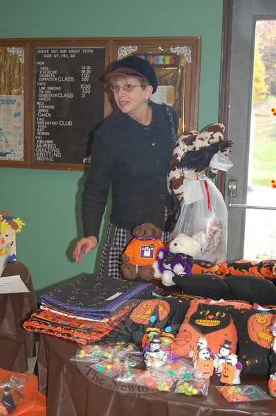 "Her arms full of treasures purchased at the Newtown Senior Center's Autumn Bazaar on Friday, October 23, shopper Marjorie Eneri Czarsty was distracted by yet another table full of handcrafted items. This year's bazaar, held Friday through Sunday, October 23-25, was ""the best year yet,"" according to Senior Center Director Marilyn Place.  (Crevier photo)"