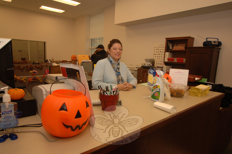 Debbie Aurelia stands behind the counter of her soon-to-be-former Town Clerk office space at Edmond Town Hall.  (Bobowick photo)