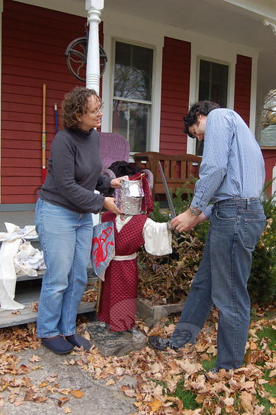 """Jessica Buster and David Turkington have amused themselves and passersby of their Sandy Hook home for the past year by dressing up an antique lawn jockey named Charlie, near the front steps of the house. Here, Ms Buster and Mr Turkington pose with """"Crusader Knight Charlie.""""  (Crevier photo)"""